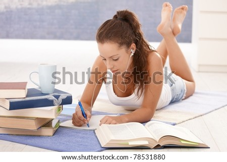 Pretty girl learning at home laying on floor, writing.? - stock photo