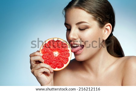 Pretty girl licking grapefruit / photoset of attractive girl holding a cut piece of Sicilian orange on blue background  - stock photo