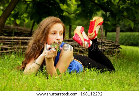 Pretty girl lies on the lawn with green grass and looks into the distance - stock photo