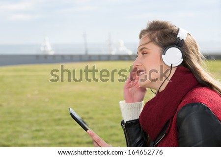 Pretty girl listening to music on a tablet - stock photo
