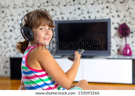 Pretty girl listening to music with headphones  in the living room  and watching tv - stock photo