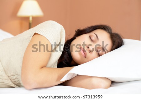 Pretty girl lying on bed and having a nap - stock photo