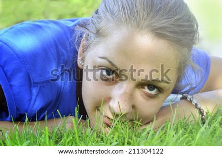 Pretty girl lying on the grass enjoying the nature, natural look lifestyle image - stock photo