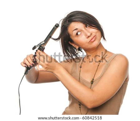 Pretty girl makes styling with hair tongs - stock photo