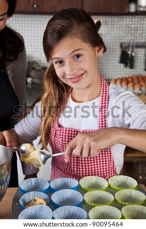 Pretty girl making cupcakes in the kitchen - stock photo