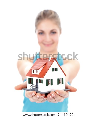 Pretty girl offering a miniature house for us - stock photo