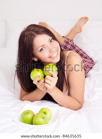 pretty girl  on the bed at home  eating apples