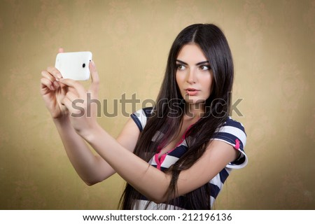 Pretty girl photographed themselves on a mobile camera. - stock photo