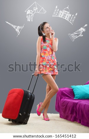 Pretty girl planning her travel abroad with chalk images against a gray background - stock photo