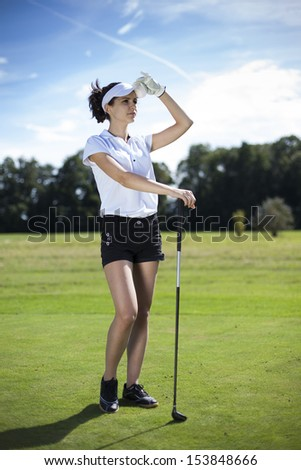 Pretty girl playing golf on grass in summer - stock photo