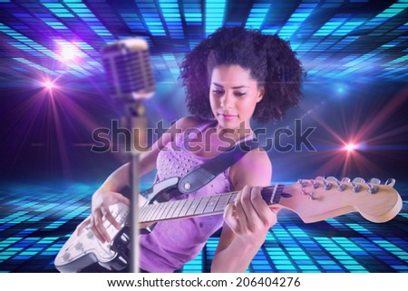 Pretty girl playing guitar against digitally generated cool disco design - stock photo