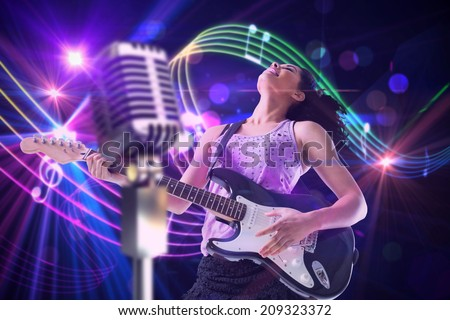 Pretty girl playing guitar against digitally generated music symbol design - stock photo