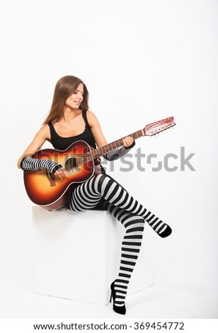 Pretty girl playing the acoustic guitar - stock photo