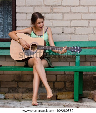 Pretty girl playing the guitar - stock photo