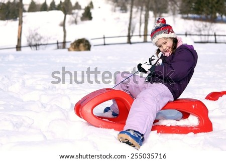 pretty girl plays with the Red sled on the snow in the winter - stock photo