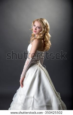 Pretty girl posing in beautiful wedding dress - stock photo