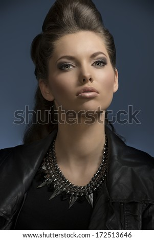 pretty girl posing in close-up fashion shoot with dark rock look and cute brown hair-style, wearing leather jacket and modern necklace looking in camera  - stock photo