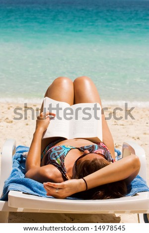Pretty girl reading novel at beautiful beach - stock photo