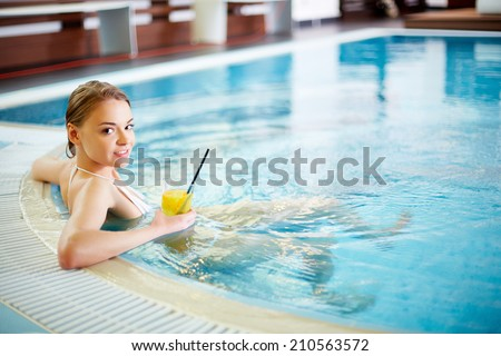 Pretty girl relaxing in swimming pool - stock photo