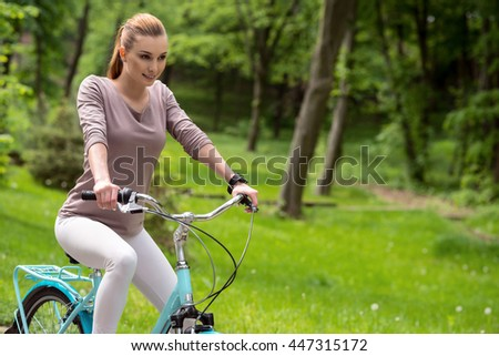 Pretty girl riding bicycle with pleasure