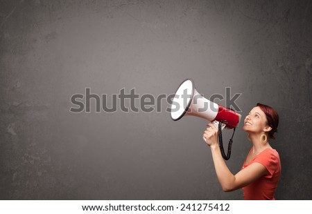 Pretty girl shouting into megaphone on copy space background - stock photo