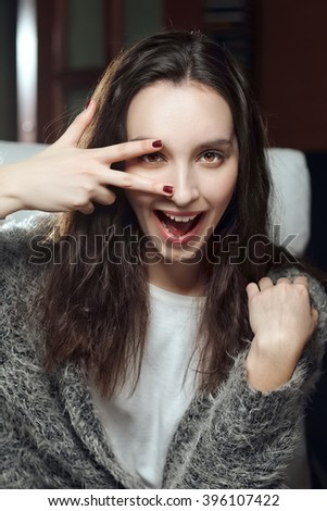 pretty girl showing V sign with fingers and screaming - stock photo