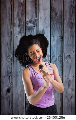 Pretty girl singing against grey wooden planks - stock photo