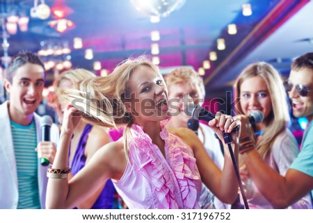 Pretty girl singing at party on background of happy friends - stock photo