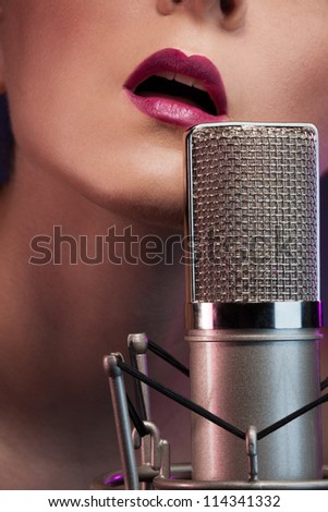 Pretty girl singing with microphone - stock photo