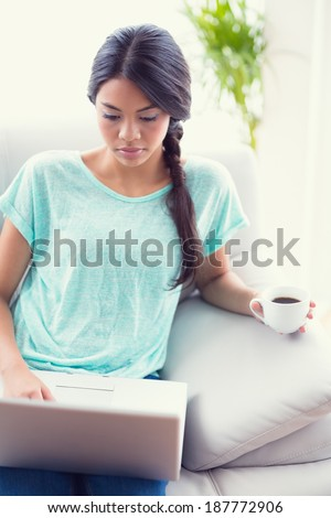 Pretty girl sitting on a sofa using laptop at home in the living room - stock photo