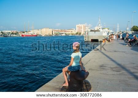 Pretty girl sitting on the beach near the sea  - stock photo