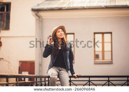 Pretty girl sitting on the railing of a warm spring day. outdoors - stock photo