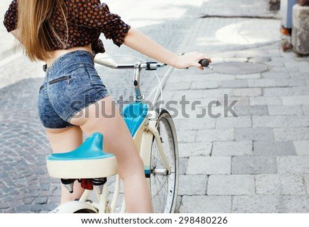 Pretty girl smiling and holding a bicycle handlebar in a sunny day on the street of the old town. Young woman with blond-brown long hair, wearing pink head wrap and pink dress with pattern of flowers - stock photo