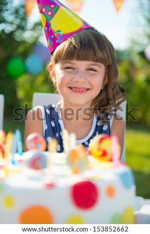 Pretty girl smiling at child's birthday party  - stock photo