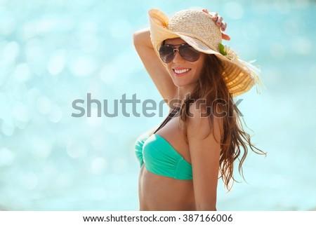 Pretty girl standing on a beach in a bikini and enjoying the sun - stock photo