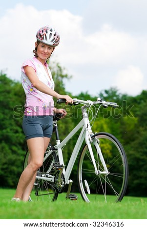 Pretty girl standing with a bicycle - stock photo