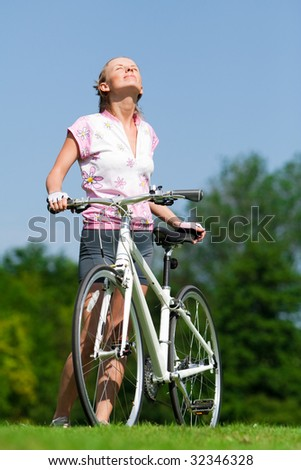 Pretty girl standing with a bicycle and enjoing the sun - stock photo