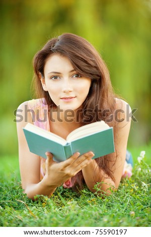 Pretty girl-student is on the lawn and read a textbook. - stock photo