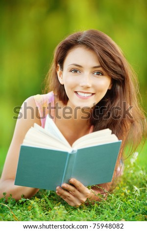 Pretty girl-student is on the lawn and read a textbook.