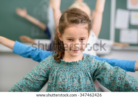 Pretty Girl Take a Lead to her Classmates While Doing an Exercise Activity Inside the Classroom. - stock photo
