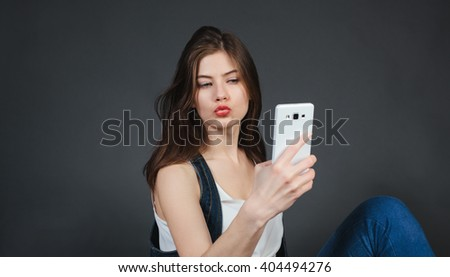 Pretty girl taking selfie and making duck face. Sending kisses and holding peace sign. Instagram