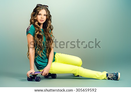 Pretty girl teenager wearing casual clothes posing with her skateboard. Active lifestyle. Studio shot. - stock photo