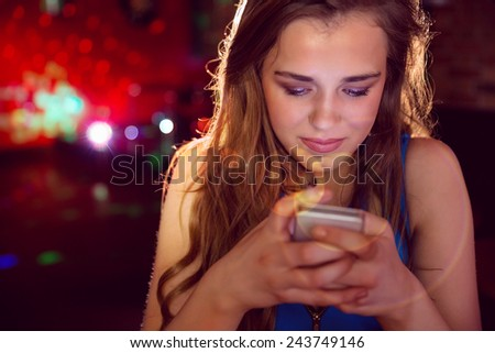 Pretty girl texting on her phone at the nightclub - stock photo