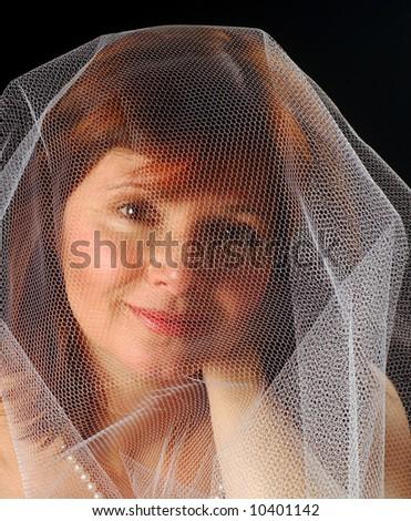 Pretty girl under a veil-like gauze, like a bride - stock photo