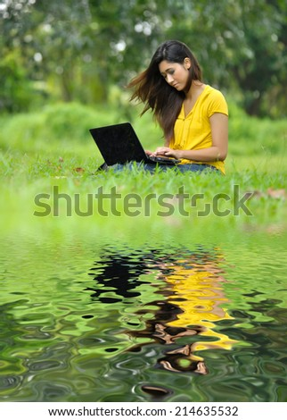 pretty girl using laptop reflected on lake - stock photo