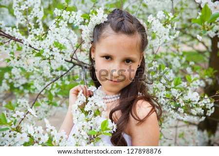 Pretty girl walking in the garden next to the blooming cherry tree
