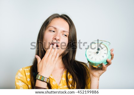 pretty girl wants to sleep, yawning with a retro alarm clock, photo studio, isolated