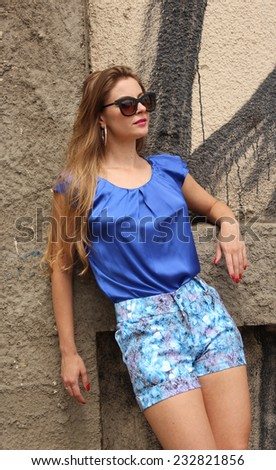 Pretty girl wearing a blue dress posing on the wall - stock photo