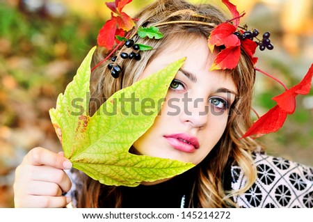 pretty girl wearing autumn crown holding leaf - stock photo