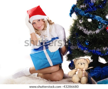 pretty girl wearing knitted mittens and santa hat sitting under christmas tree with gifts - stock photo
